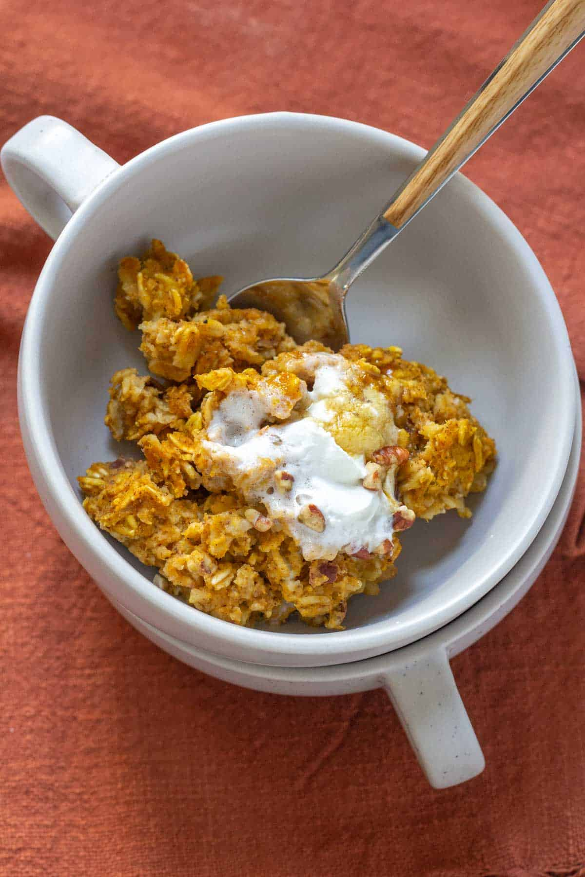 overhead pumpkin baked oatmeal in a bowl with a spoon