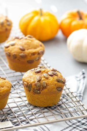 pumpkin muffins with spiced pepitas topping on a wire cooling rack