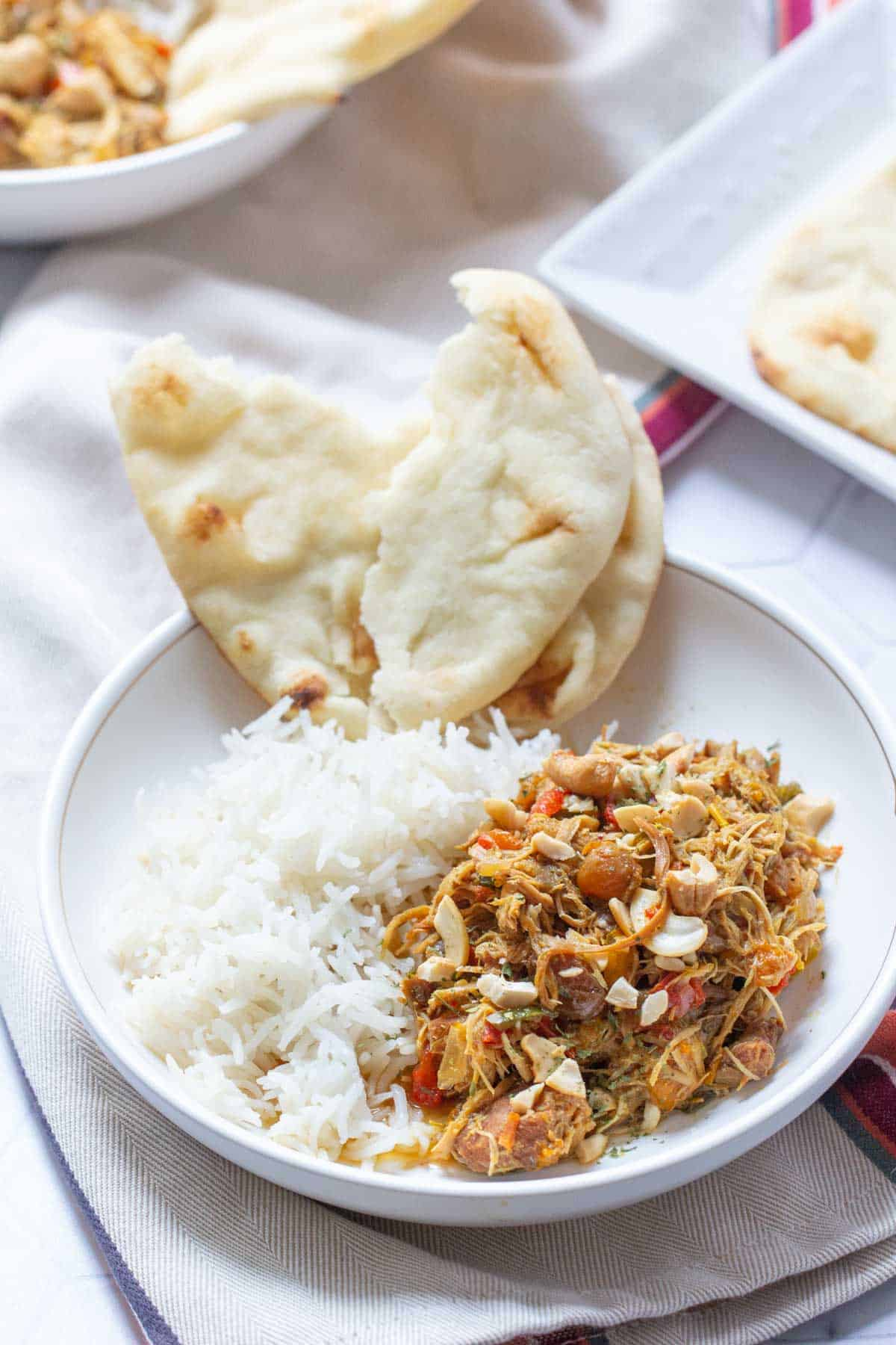 bowl of curried chicken with rice and naan