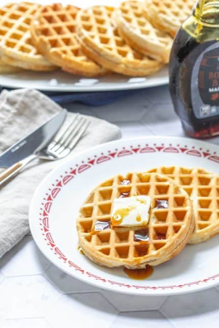 plate of peanut butter waffles with butter and syrup